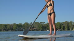 Slow motion shot of young woman sup stand-up paddleboarding on a lake, slow moti Stock Footage