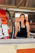 Portrait of woman at hatch of food stall trailer Stock Photos