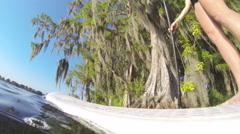 Young woman sitting on her sup board while stand-up paddleboarding on a lake. Stock Footage