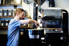 Young man putting in handful of coffee beans to coffee roaster in cafe Stock Photos