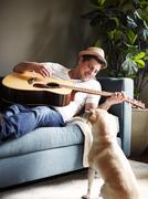 Cool mid adult man playing acoustic guitar on sofa, watched by dog Stock Photos