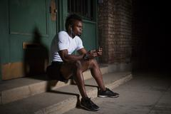 Young man with mohawk, sitting on steps at night, wearing earphones Stock Photos