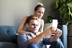 Couple relaxing on sofa reading smartphone message Stock Photos
