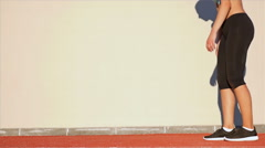 Track runner woman and her shadow on a wall preparing to run Stock Footage