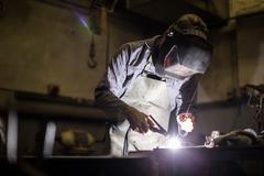 Welder wearing welding mask welding Stock Photos