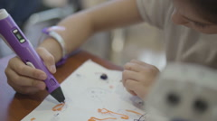 Close up of a young girl dipping her brush in paint and painting on a canvas Stock Footage
