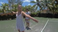 A boyfriend teaching his girlfriend how to play tennis while on vacation. Stock Footage