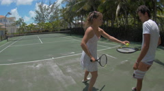 A young couple playing tennis together while on vacation. Stock Footage