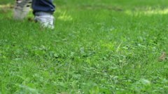 foot of man walk quickly on a lawn Stock Footage