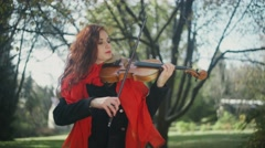 Beautiful girl with red hair, with bright lipstick plays on violin Stock Footage