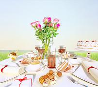 Afternoon tea and delicious dessert on the background of nature. Stock Illustration