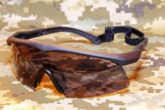 Military tactical goggles on camouflage background taken closeup Stock Photos