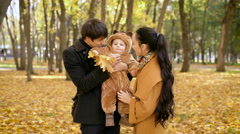Family in the forest. Baby boy with autumn leaves in his hand, in the arms of Stock Footage