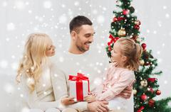 Happy family at home with christmas tree Stock Photos