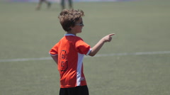 Young boy in orange uniform playing in a youth soccer league game. Stock Footage