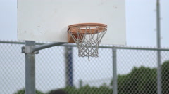 Young man basketball player shooting hoops on an outdoor street basketball court Stock Footage