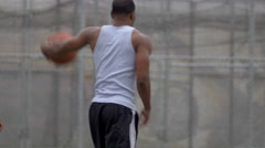 Two young men shooting hoops together on an outdoor basketball court. Stock Footage