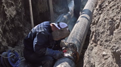 Welder  in the Earthen Trench Welds Pipes Stock Footage