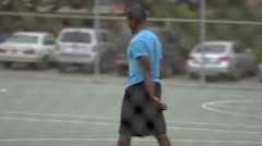 Two young men playing one-on-one basketball together on an outdoor court surroun Stock Footage