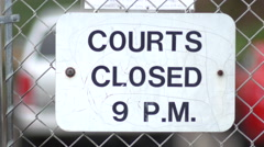 Basketball court hours sign on chain link fence surrounding outdoor court. Stock Footage