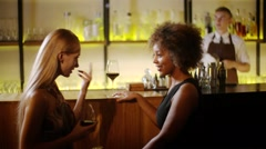 Two girls chatting and drinking red wine at the luxury bar. At background barman Stock Footage