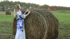Blonde girl in a long dress near the straw sheaves Stock Footage
