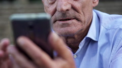 Elderly man intent on using  mobile phone Stock Footage