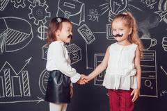 Two little girls as with mustache standing on dark background of painted wall Stock Photos