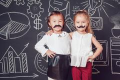 Two little girls as with mustache standing embracing on dark background of Stock Photos