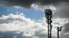 Football stadium spotlights turned off with overcast sky in background Stock Footage