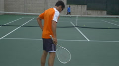 A experienced tennis player serving to a beginner tennis player, slow motion. Stock Footage