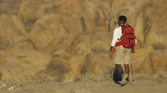 A young man backpacking in a mountainous desert. Stock Footage