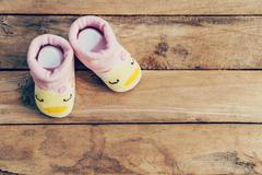 Baby shoes on wooden background with space Stock Photos