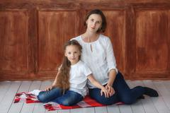 Little girl and her pregnant mom sitting in studio Stock Photos