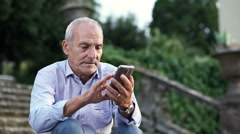 Retired man  only to the park typing on mobile Stock Footage