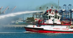 Fireboat from fire department sprays jets of water from cannon at sea port 4K Stock Footage