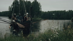 Viking Warriors Jump off the Row Ship Stock Footage