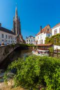 BRUGES, BELGIUM - APRIL 6, 2008: Tourists float on a boat l near  Dijver brid Stock Photos