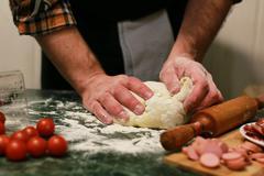 Man hand prepare pizza dough topping Stock Photos