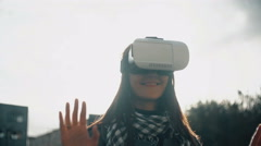 Woman uses a virtual reality glasses in rear light at sunset 4k Stock Footage