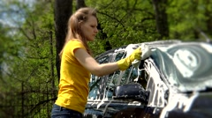 Beautiful girl washes her car with sponge Stock Footage