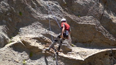 A young man repelling down a mountain while rock climbing , slow motion. Stock Footage