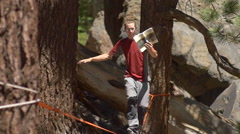 A man balancing on a slackline while reading a book, slow motion. Stock Footage