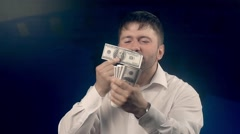 Happy man feels delight looking through a roll of bills Stock Footage