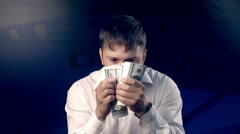 Young man looks back while counting a big amount of money Stock Footage
