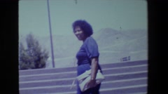 1981: two women walking up steps against a mountainous background LANSING Stock Footage