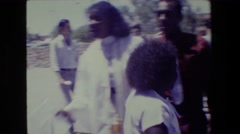 1981: a black, female graduate wearing a graduation robe poses with her family Stock Footage