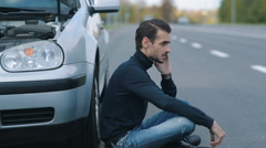 Man siitting near broken car and calling for help Stock Footage