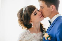 Bride and groom in studio light stand kiss on a white background Stock Photos