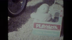 1981: baby being dragged through grass in playskool toy box by adult LANSING Stock Footage